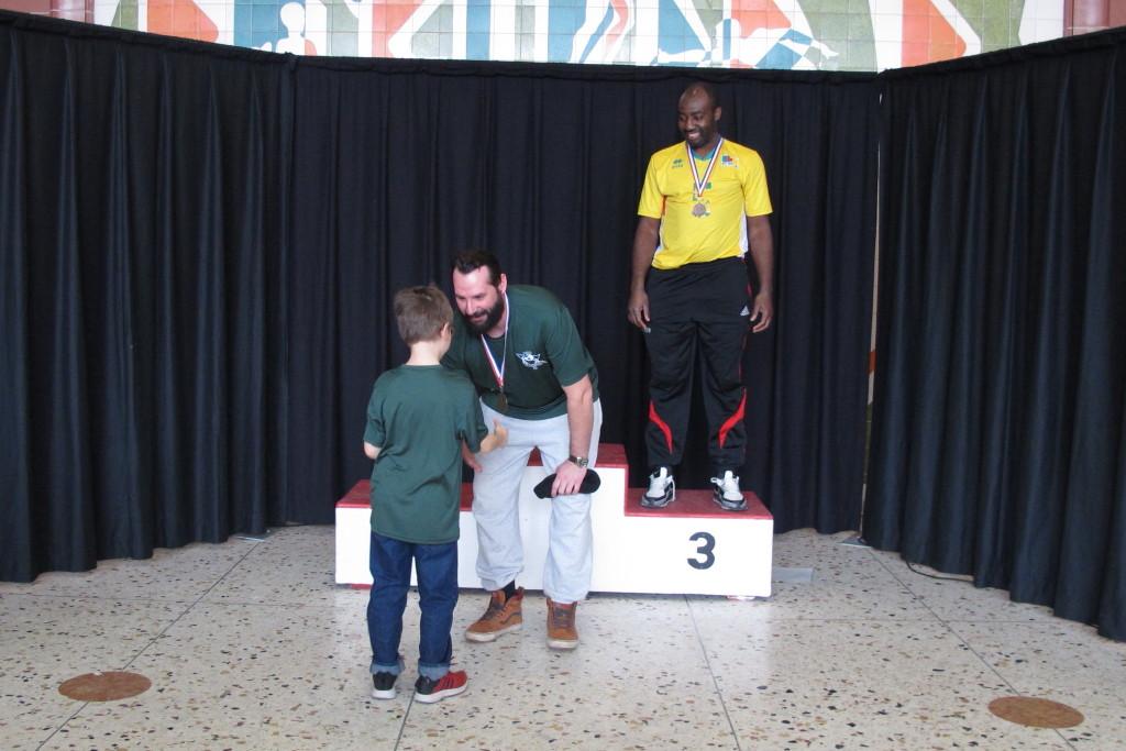 Matthieu reçoit la médaille d'or des mains d'Émile.  Ricardo médaille de bronze.